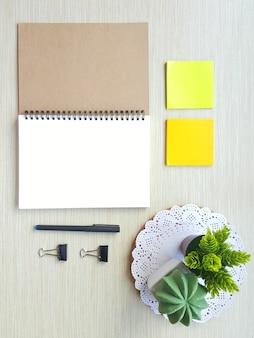 Un cuaderno de espiral en blanco con papelería de oficina puso en el fondo de la mesa de madera