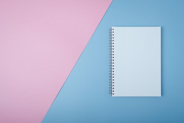 Cuaderno espiral en blanco sobre fondo pastel