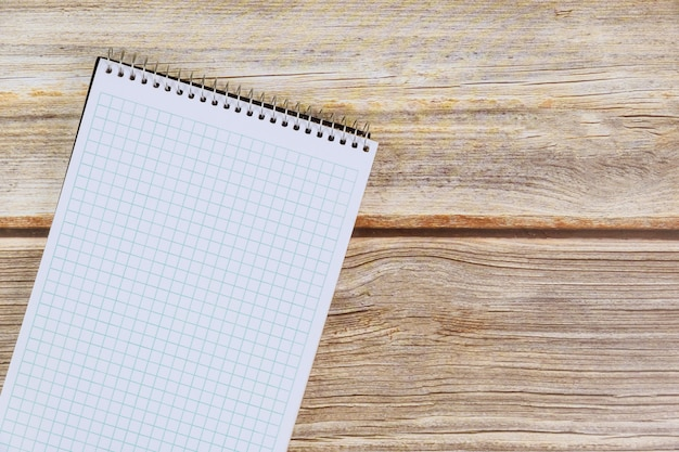 Cuaderno espiral en blanco sobre mesa de madera