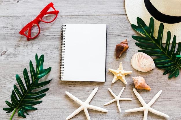 Cuaderno espiral con concha marina, hoja, sombrero de paja, gafas de sol y estrellas de mar en la mesa