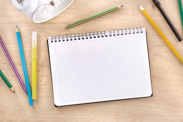 Cuaderno espiral escolar con marcadores sobre fondo de madera vista superior