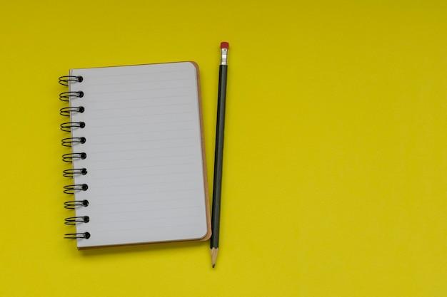 Cuaderno de espiral con hojas blancas y lápices sobre fondo amarillo