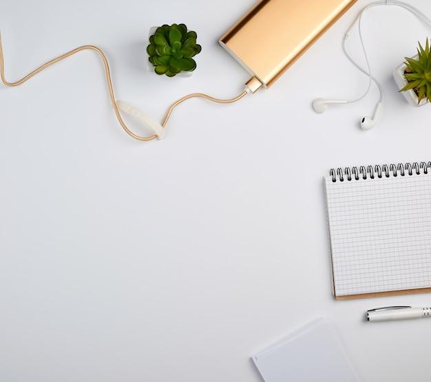 Cuaderno espiral con hojas blancas vacías, bolígrafo y plantas verdes.