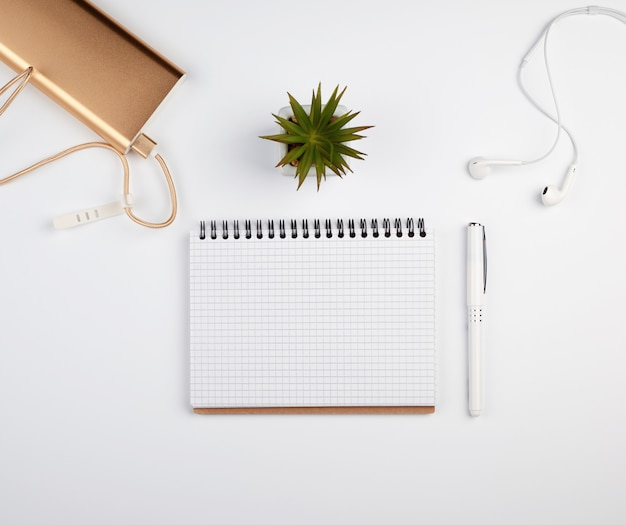 Cuaderno espiral con hojas vacías, bolígrafo y plantas verdes.