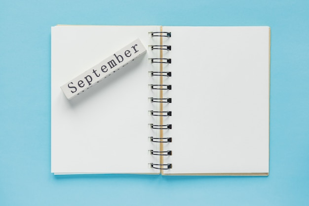 Cuaderno espiral limpio para notas y mensajes y barra de calendario de madera de septiembre en azul