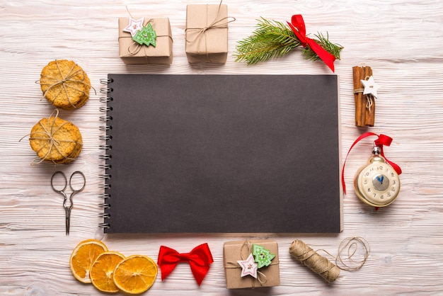 Cuaderno espiral negro sobre fondo de madera, concepto de navidad, espacio de copia
