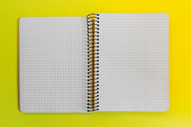 Cuaderno espiral de papel en blanco sobre amarillo