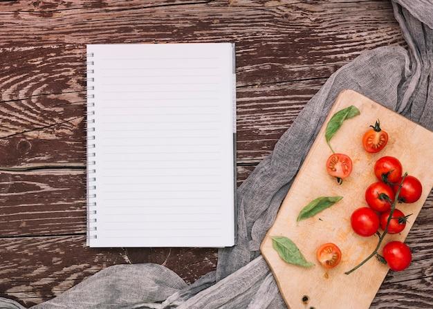 Cuaderno espiral de una sola línea; tomates cherry y albahaca en tabla de cortar sobre la mesa de madera