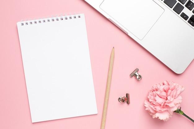 Cuaderno con flor de clavel rosa sobre un fondo de mármol