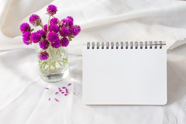 Cuaderno y flor violeta sobre mesa.