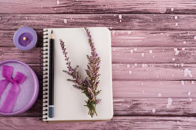 Cuaderno, flores de brezo, vela