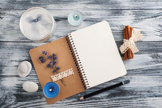 Cuaderno, flores de lavanda, velas, guijarros
