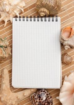 Cuaderno en el fondo de esteras y conchas de mar