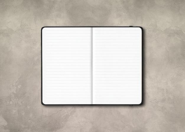 Cuaderno forrado abierto negro aislado sobre fondo de hormigón