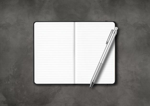 Cuaderno forrado abierto negro con un bolígrafo aislado sobre fondo de hormigón oscuro