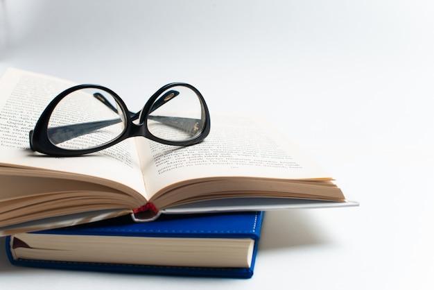 Cuaderno con gafas y pluma, libro con gafas, cuaderno azul con gafas, libro con taza de té