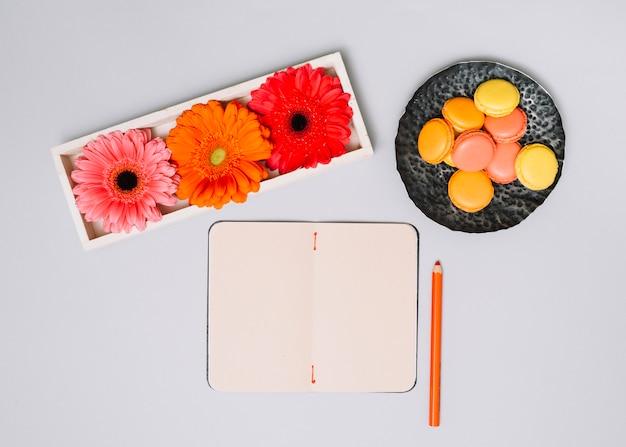 Cuaderno con galletas y flores brillantes en mesa blanca