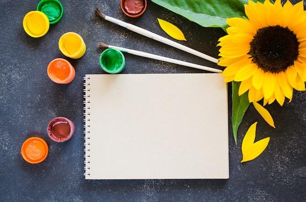 Cuaderno con girasol y pintura artística, vista superior