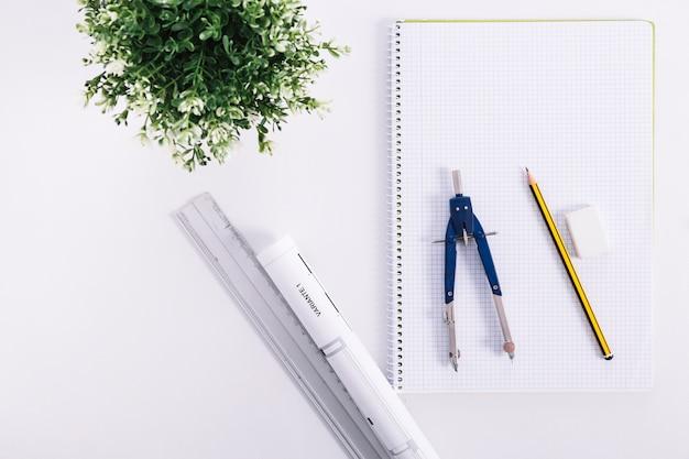 Cuaderno y herramientas de medición cerca de la planta