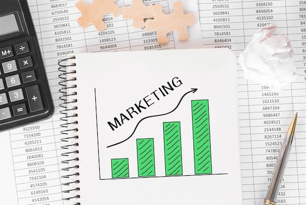 Cuaderno con herramientas y notas sobre estrategia de marketing, concepto.