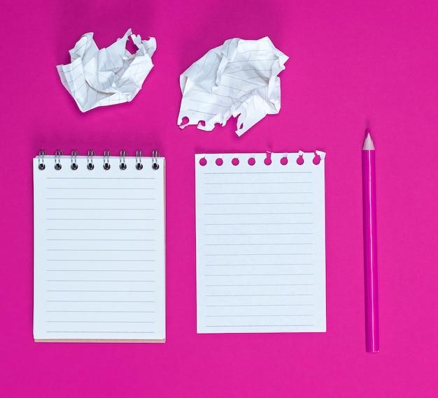 Cuaderno con hojas blancas vacías, dos hojas de papel arrugadas