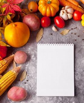 Cuaderno con hojas de otoño y verduras en el fondo de hormigón