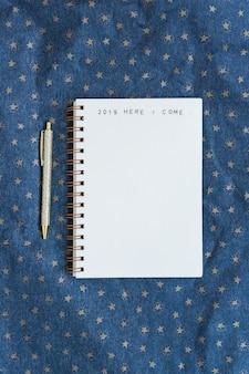 Cuaderno con inscripción cerca de pluma