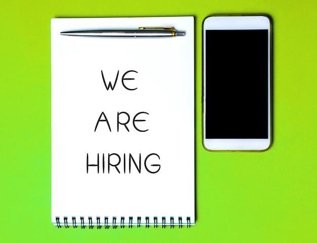 Cuaderno con la inscripción estamos contratando un bolígrafo y un teléfono búsqueda de empleados