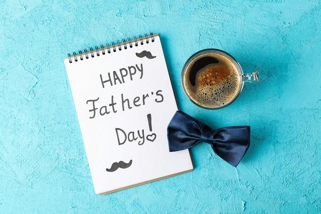 Cuaderno con inscripción feliz día del padre, pajarita azul y taza de café sobre fondo de color, espacio para texto y vista superior