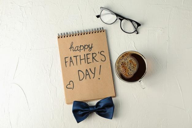 Cuaderno con inscripción feliz día del padre, pajarita azul, taza de café y vasos sobre fondo blanco.