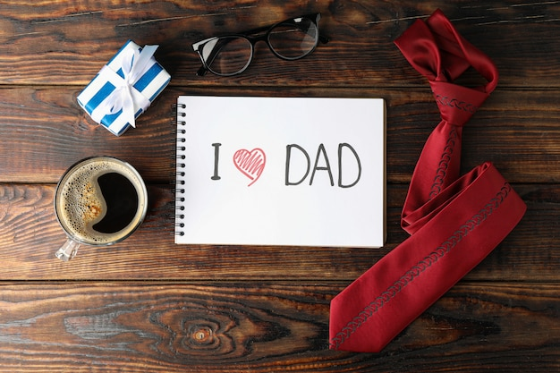 Cuaderno con inscripción me encanta dad, taza de café, vasos, caja de regalo y corbata sobre fondo de madera