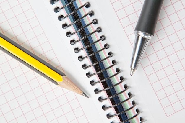 Cuaderno en una jaula con un bolígrafo y lápiz.