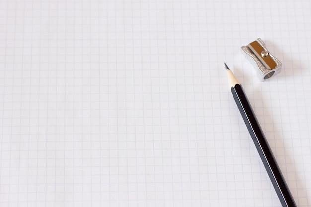 Cuaderno en una jaula con un lápiz en primer plano, en blanco para el diseñador, plan de negocios