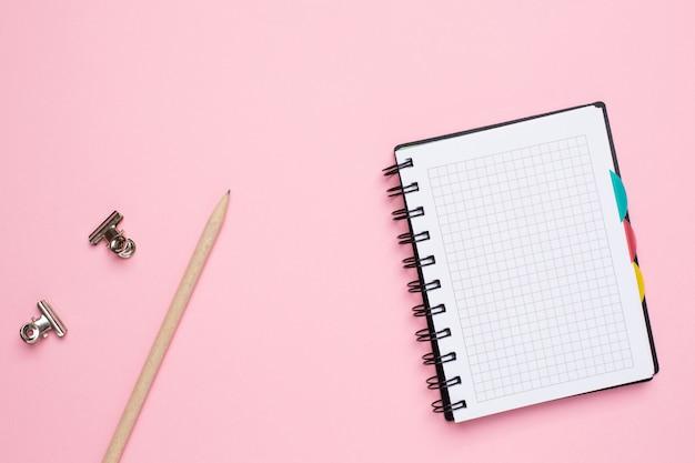 Cuaderno en una jaula con lápiz sobre un fondo rosa