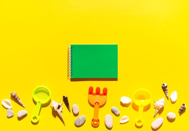 Cuaderno y juguetes de playa.