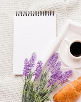 Cuaderno junto a la bandeja con desayuno