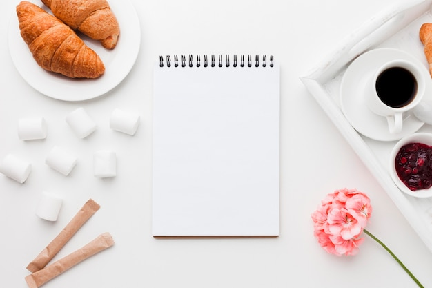 Cuaderno junto a la bandeja con taza de café y croissant