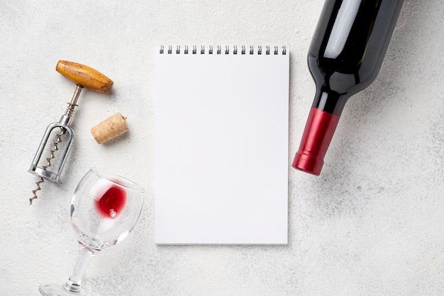 Cuaderno junto a la botella de vino y vasos