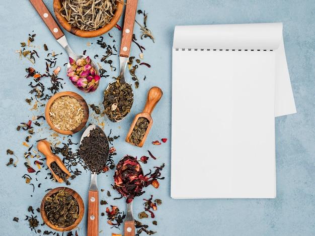 Cuaderno junto a la cuchara y tazones con té de hierbas