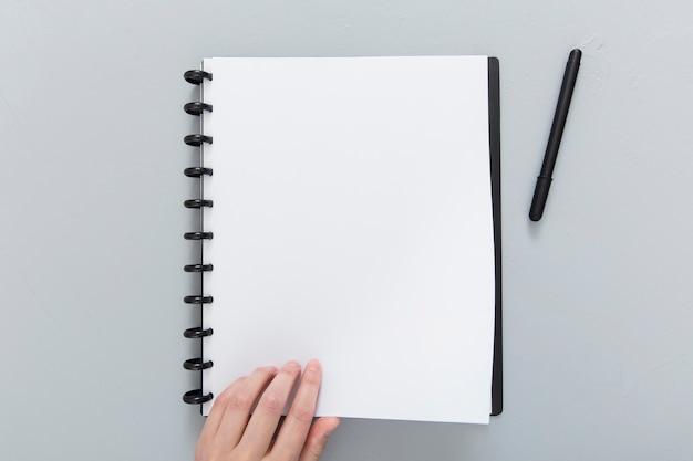 Cuaderno con lapicero en escritorio