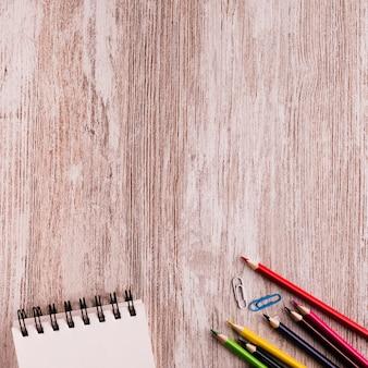 Cuaderno con lápices en superficie de madera