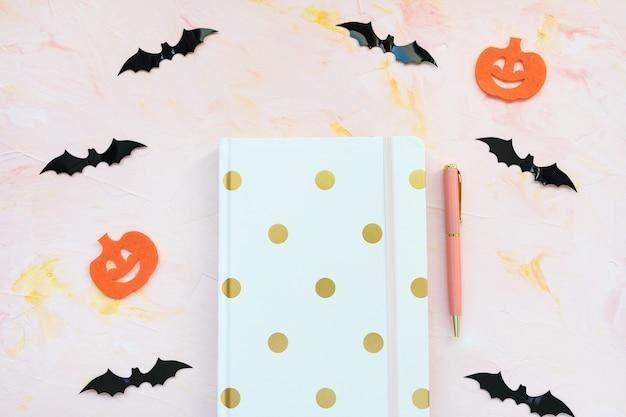Cuaderno lápiz calabazas y murciélagos sobre un fondo rosa concepto de halloween