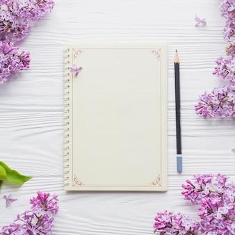Cuaderno y lápiz cerca de lila