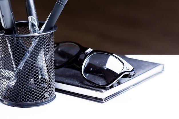 Cuaderno, lapiz y gafas.