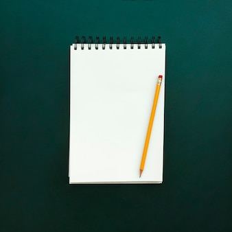 Cuaderno con lápiz en pizarra verde de regreso a la escuela