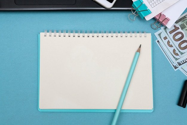 Cuaderno con lápiz sobre un escritorio azul
