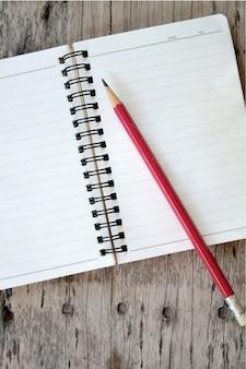 Cuaderno y lápiz sobre fondo de madera vieja.