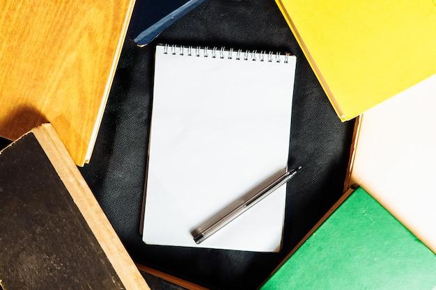 Cuaderno con libros en la superficie y bolígrafo