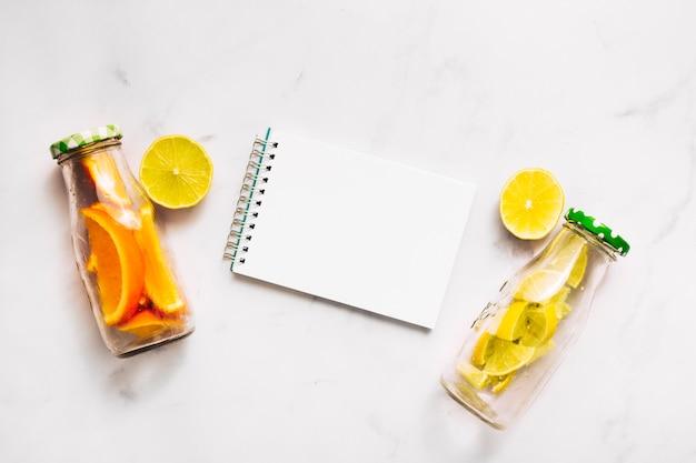 Cuaderno de lima en rodajas y botellas de vidrio con cítricos cortados.