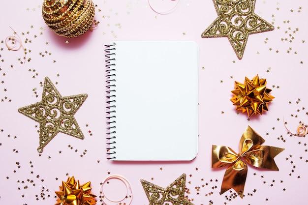 Cuaderno limpio para objetivos o lista de tiendas navideñas y resoluciones sobre fondo rosa con estrellas doradas decorativas y confeti